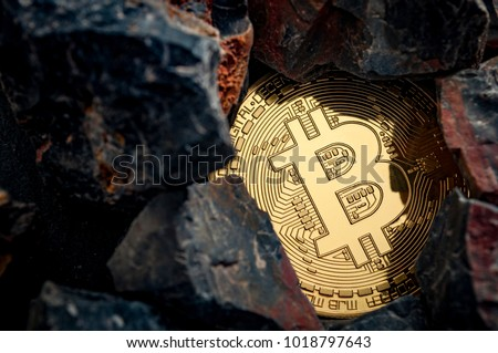 Bitcoin mining and cryptocurrency concept with a golden coin submerged in black stones compared to the traditional gold mining #1018797643