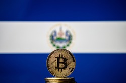 Bitcoin representation coin placed in front of blurred Salvador's national flag. El Salvador is the first country to adopt bitcoin as legal tender. Concept.