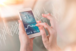 Bitcoin symbol on mobile app screen with big BUY and SELL buttons. Bitcoin on stock market. New digital money.