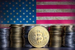 Bitcoin token infront of currency coins and grungy flag of the united states.