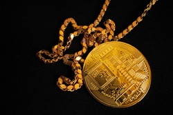 bitcoin token visible with gold chain on black background