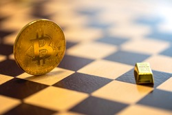 Bitcoin vs gold concept - bitcoin coin and small gold bar on chessboard. Selective focus on the word gold