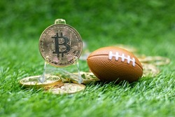 Bitcoin with American Football is on green grass for betting concept