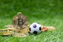 Bitcoin with soccer ball is on green grass for sport betting concept