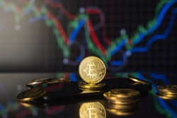 Bitcoins and virtual money concept. Gold bitcoins on a stack of coins with chart of growing and falling valuance of a cryptocurrency. Mining or blockchain technology.