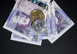Bitcoins on top of english pounds as great britain money versus internet crypto currency concept