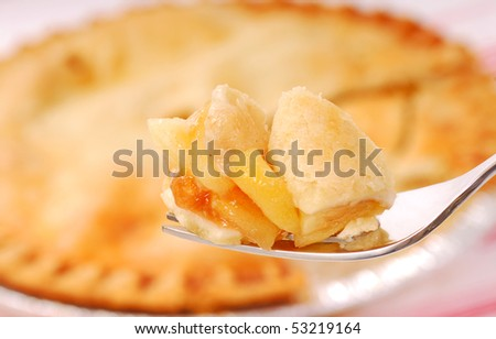 Bite of freshly baked apple pie on a fork