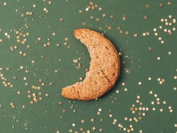 Bite of moon shape cookie biscuit with gold glitter stars on green background. Crescent creative concept.