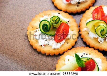 Bite size canapes with ricotta cheese, zuchinni and tomato