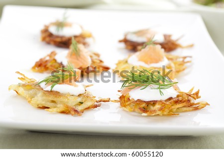 Bite sized potato rosti appetizer topped with fresh sour cream, smoked salmon and dill.