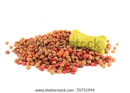 Bits of dog food lying on a white background with green rubber toy bone