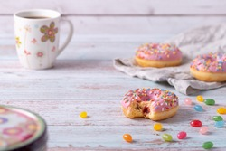 Bitten delicious strawberry donuts with pink icing, colorful sprinkles and jelly beans on wooden background. Sweet pastry as a snack for children's birthday party or other celebrations. Pastel colors.