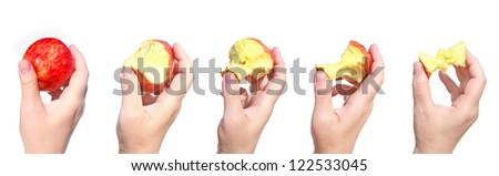 Bitten off a red ripe apple in the hand - stages of eating apple isolated on white