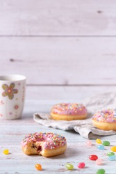 Bitten strawberry donuts with pink icing, colorful sprinkles and jelly beans on wooden background. Sweet pastry as a snack for children's birthday party or other celebrations. Copy space.