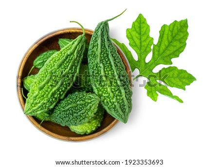 Bitter gourd ( bitter cucumber, Momordica Charantia, bitter melon ) in wooden bowl with green leaf isolated on white background.  Top view. Flat lay.