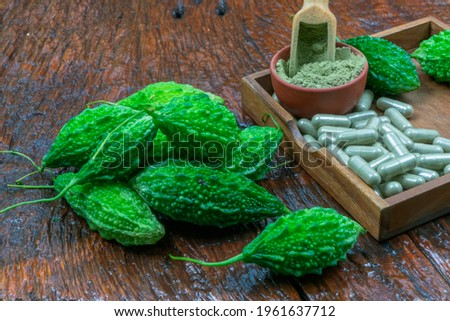 Bitter gourd, extract powder bitter gourd, and herbal capsule on wooden background, bitter gourd to strengthen the immune system (Momordica charantia).