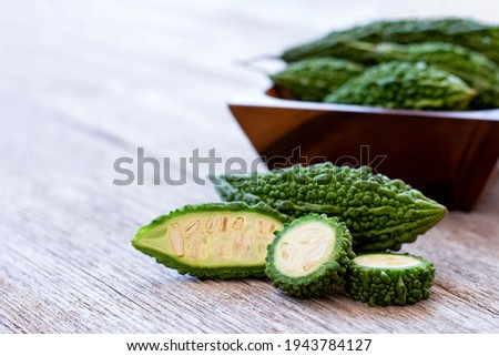 Bitter melon ( bitter cucumber ) in wooden bowl on wood table background.