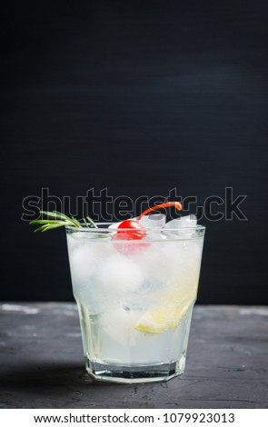 Bitter old-fashioned cocktail with lemon slice and cherry. Selective focus.