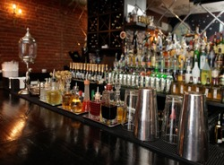 Bitters and infusions on bar counter with blurred bottles in background