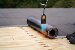 Bitumen roofing.  A with a gas burner and a roll of tar paper. Flat roof installation.