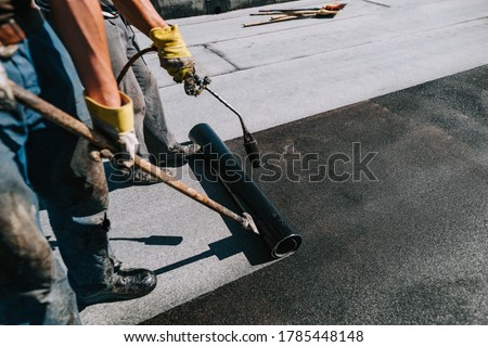 Photo of  Bituminous membrane waterproofing system details and installation on flat rooftop. Professional construction worker  installing and waterproofing flat roof at house construction site.