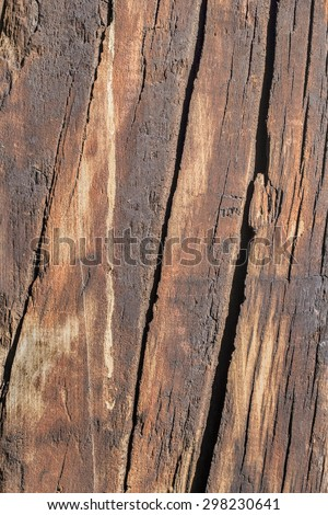 Bituminous surface texture of an old weathered, rotten, cracked Square Timber Bollard, made of obsolete, scrapped Railroad Cross Tie Timber.