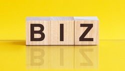 biz word written on wood block. office word is made of wooden building blocks lying on the yellow table