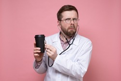 Bizarre doctor listens to the paper mug with a stethoscope and is surprised. Pink background.