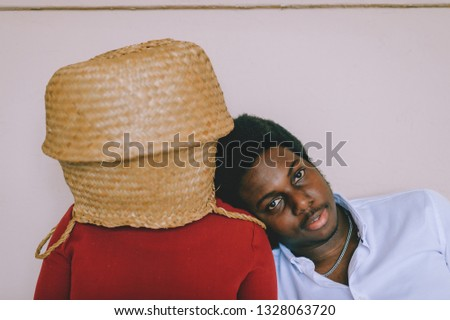 Bizarre interracial loving couple. Dark skinned african man with smiling face sit with his caucasian unrecognizable girlfriend with straw basket on her head at home. Weird intternational relationship