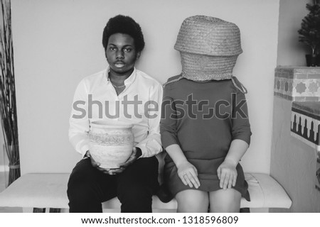 Bizarre interracial loving couple. Dark skinned african man with smiling face sitting with his caucasian unrecognizable girlfriend with straw basket on head at home. Weird intternational relationship.