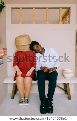 Bizarre interracial loving couple. Dark skinned african man with smiling face sitting with his caucasian unrecognizable girlfriend with straw basket on head at home. Weird intternational relationship