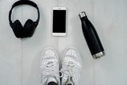Black a headphones and white smartphone with sports sneakers shoes, bottle of water on a woodenbackground, top view, flat lay photo