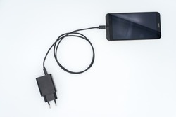 Black AC charger and USB cable connected to black mobile phone on white background.