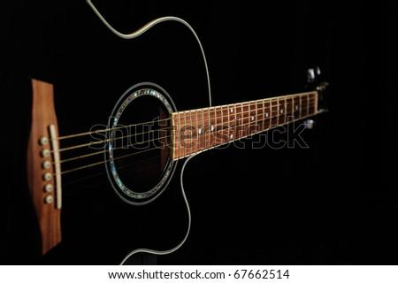 Black acoustic guitar over black background