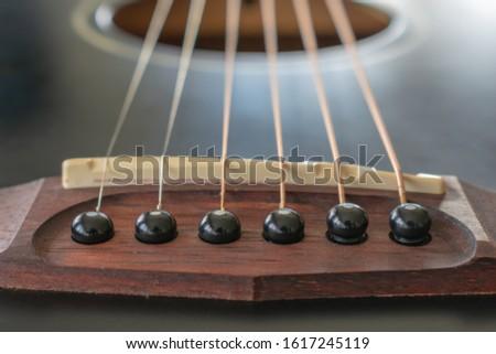 Black acoustic guitar strings attachment