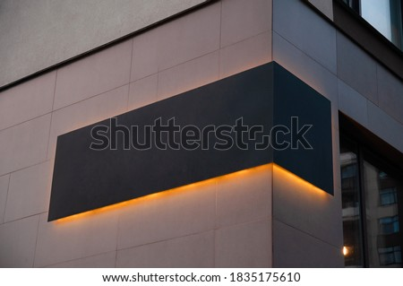 black advertising board with yellow led glow  on the corver of building, company sign on wall. Place for text Stockfoto ©