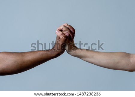 Black African American and Caucasian hands holding together stop racism. White and black skin arms in world unity multiracial love and understanding in tolerance and races diversity cooperation. #1487238236