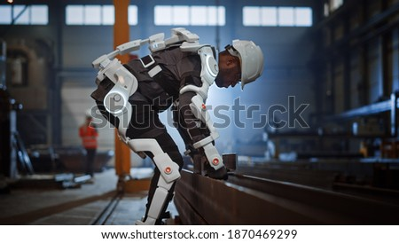 Black African American Engineer is Testing a Futuristic Bionic Exoskeleton and Picking Up Metal Objects in a Heavy Steel Industry Factory. Contractor is Heavy Lifting Steel Parts in a Powered Shell.