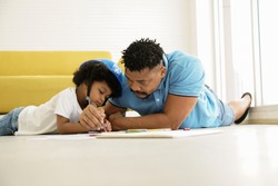 Black African American family father and son drawing and lay on the floor at home. Young father holding his little boy hand, holding a pencil to teach drawing and painting on paper