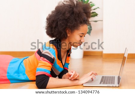 Black African American student teenage girl with a afro haircut seated on the floor using a laptop computer