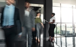 Black african business woman standing with paperwork, waiting to enter a busy elevator lift. With people walking out in a blur, showing motion.
