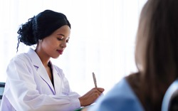 Black African doctor talking to recovering patient in hospital. Recovering patient consulting with doctor about medical treatment & coronavirus outbreak. Health Insurance & recovering patient concept.