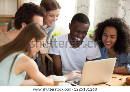 Stock Photo Black african guy with diverse friends watching comedy movie funny videos online using computer sitting together at desk. Friendship between multiracial people and leisure free time activities concept