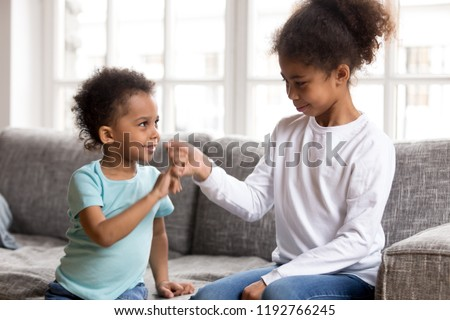 Black African little brother and sister sitting on couch at home. Small american children reconcile after fight or quarrelling making peace with hand gesture joining pinkies swear be friends forever