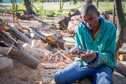 black african male in south africa carves a wooden heart using an angle grinder