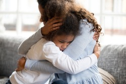 Black African mother embrace little preschool frustrated kid sitting on couch together at home. American loving mother supports disappointed daughter sympathizing, making peace after scolding concept