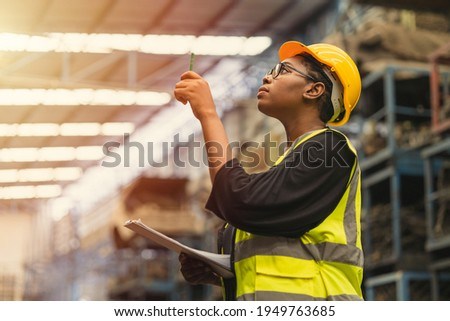 Black African professional women worker working count checking inventory production stock control in business factory  industry warehouse waring engineer suit and helmet for safety Foto stock ©