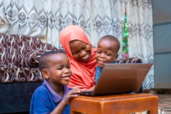black african single mother with two little preschool sons sitting using computer watching cartoon,online surfing internet