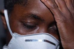 Black African woman with eyes close and hand over one side of her head. She is wearing a protective white face mask.