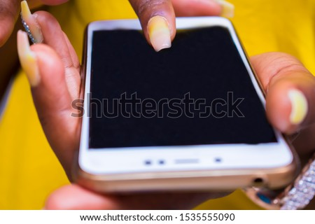 Black African women using a touchscreen display phone chatting with friends on social media #1535555090